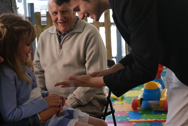 La cara de una niña y su abuelo ilusionadas en un cumpleaños.
